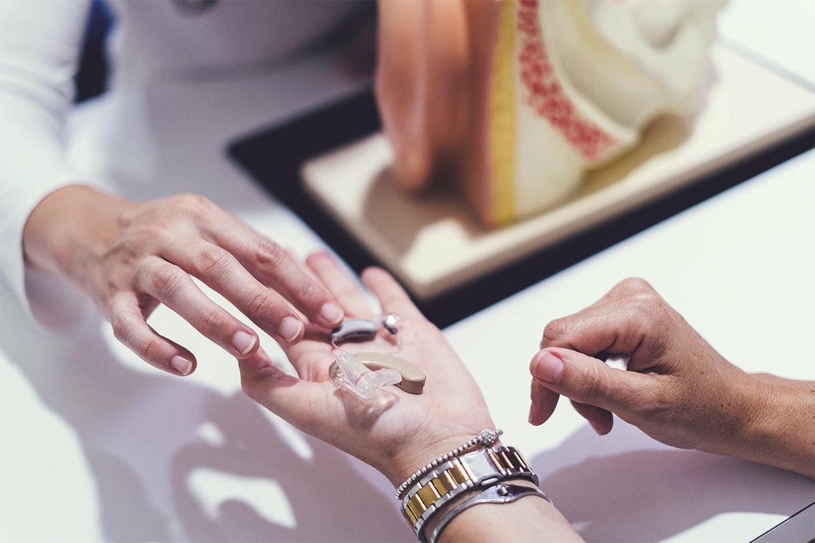 Ein Hörgerät wird einer Kundin in die Hand gelegt.