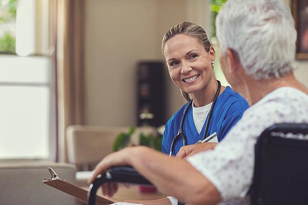 Eine Frau im medizinischen Kittel spricht mit einer älteren Dame.